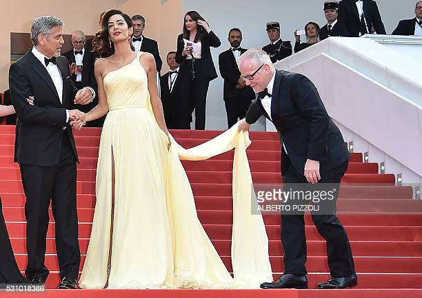 Cannes Film festival General Delegate Thierry Fremaux adjusts on May 12 2016 BritishLebanese lawyer Amal Clooney's dress as she arrives with her...