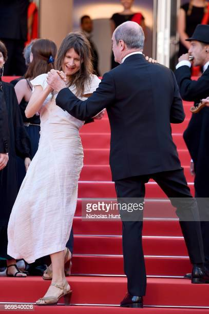 Cannes Film Festival President Pierre Lescure dances with a woman as musicians play on the red carpet before the screening of 'Capharnaum' during the...