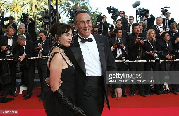 French tv presenter and producer Thierry Ardisson and his wife sound mixer Beatrice smile 27 May 2007 upon arriving with an unidentified guest at the...