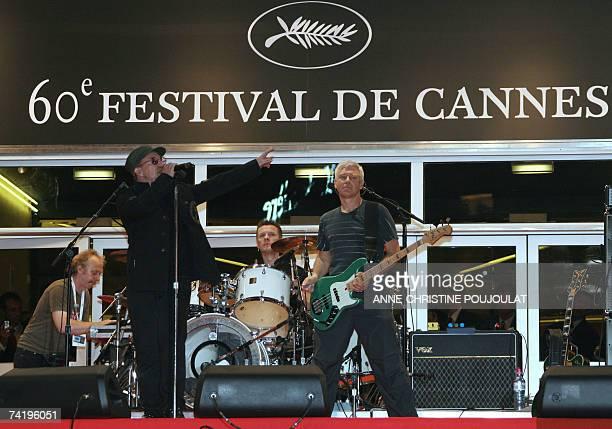 Irish rock band U2's lead singer Bono performs early 20 May 2007 next to fellow band member British bass player Adam Clayton and Irish drummer Larry...
