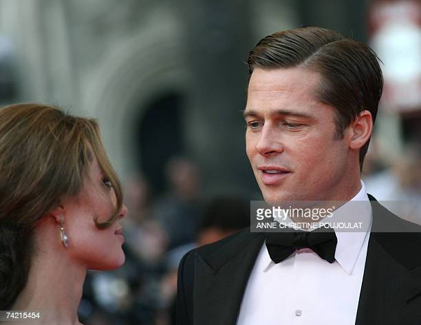 US actor and producer Brad Pitt looks 21 May 2007 at actress Angelina Jolie as they arrive at the Festival Palace in Cannes southern France for the...