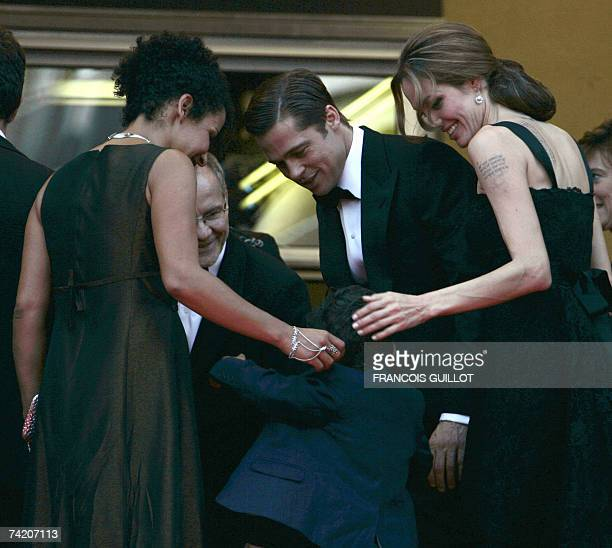 Actress Angelina Jolie and actor and producer Brad Pitt and Cannes Film Festival director Thierry Fremaux play 21 May 2007 with French journalist and...