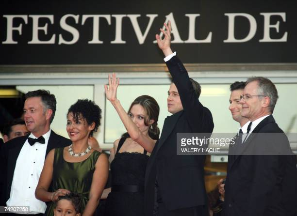 Actress Angelina Jolie and actor and producer Brad Pitt waves to fans 21 May 2007 as they pose with British director Michael Winterbottom , French...