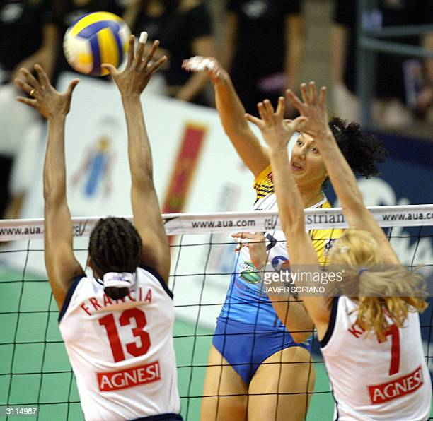 Cannes' Italian Simona Rinieri spikes on the block of Sirio Perugia's Croatian Irina Kirilova and Cuban Mirka Francia during their volleyball Final...