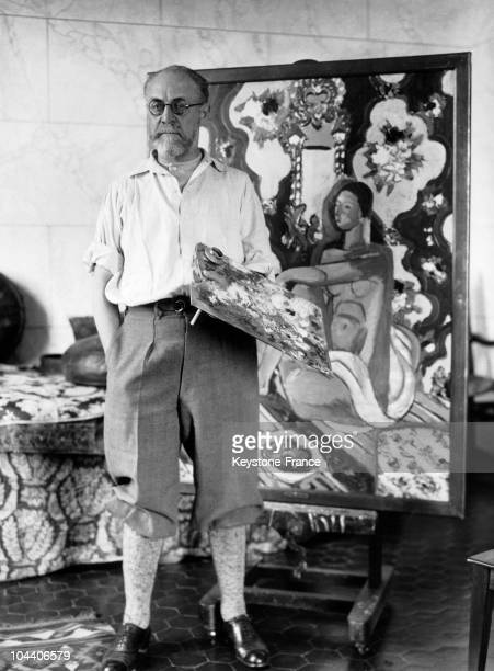 Cannes, the French painter Henri MATISSE posed in his studio. Behind him is his work FIGURE DECORATIVE SUR FOND ORNAMENTAL, painted around 1926.