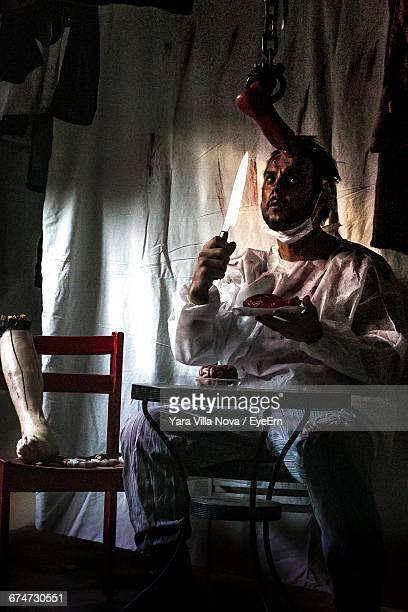 cannibal holding knife and human heart in plate - cannibalism stock photos and pictures