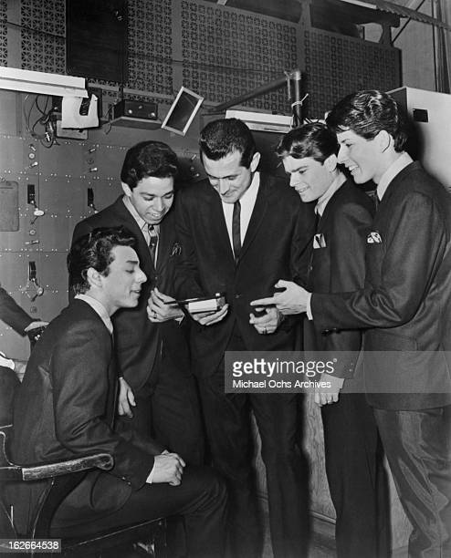 Cannibal the Headhunters pplay thier single for KRLA disc jockey Dave Hull on a mini record player backstage at The Shrine Auditorium circa 1965 in...