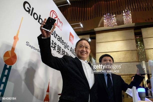 Canning Fok , group co-managing director for CK Hutchison , and Xiang Wang , senior vice president for Xiaomi, pose with mobile phones during a joint...