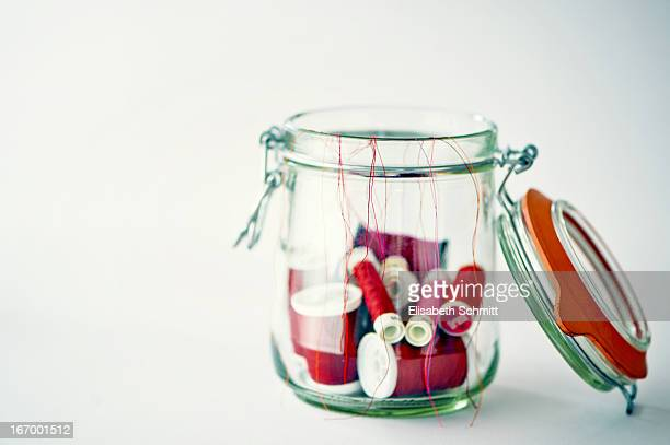 Canning jar filled with several red yarn rolls