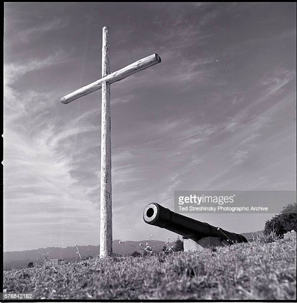 A cannon and a large wooden cross on a hill inside the Navy base in Monterey California