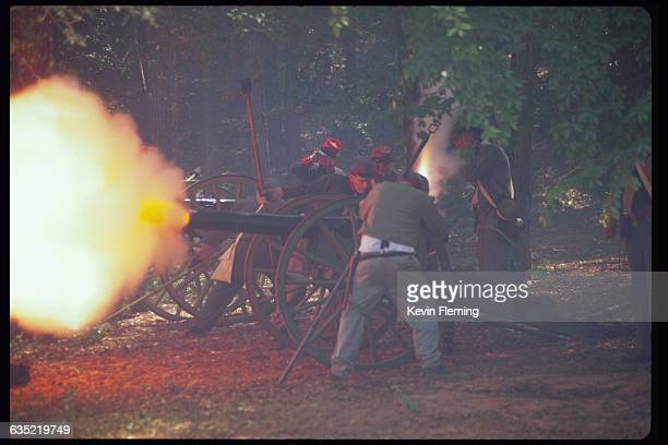 A cannon goes off in an orange flash during a reenactment of Civil Warstyle fighting at Andersonville Georgia the site of an infamous Confederate...
