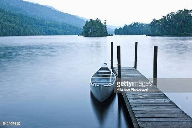 canoe at pier on lake george near st. sacrament island - image stock pictures, royalty-free photos & images