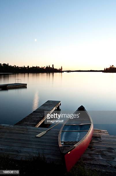 Canoe by a Dock at Sunset