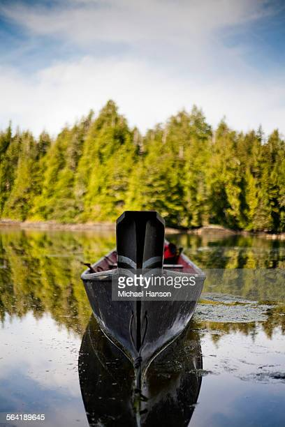 a canoe, carved with the traditions of the native peoples of vancouver island, in a small inlet near tofino. - vancouver island stock pictures, royalty-free photos & images