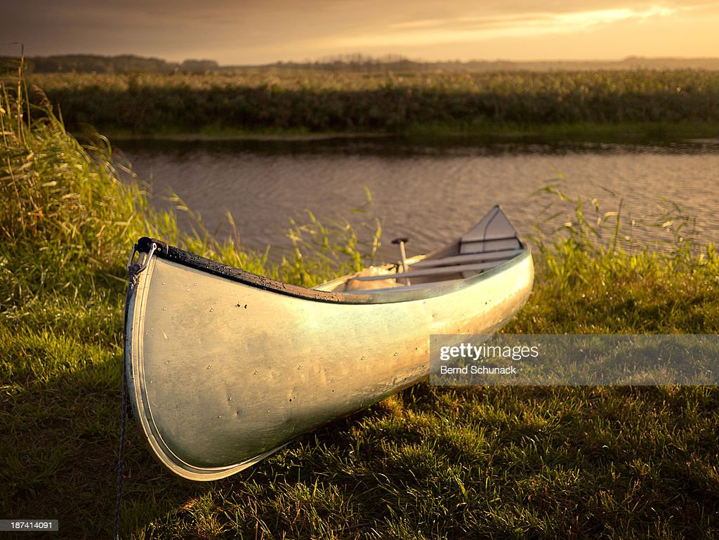 Canoe in evening light at the river bank : Stock-Foto