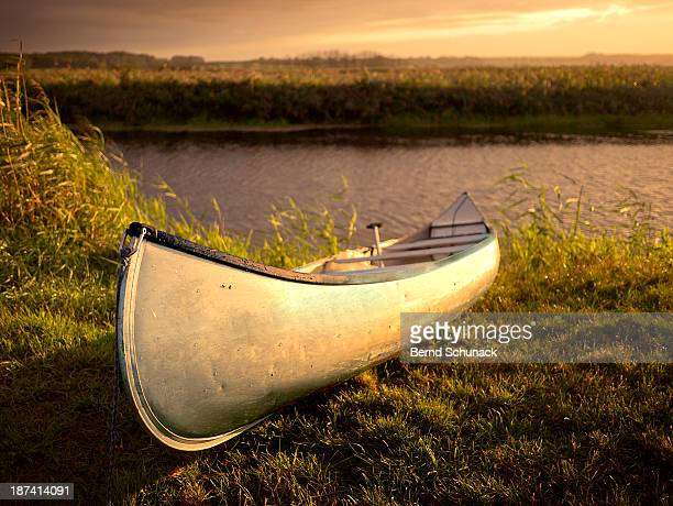 canoe in evening light at the river bank - bernd schunack stock pictures, royalty-free photos & images
