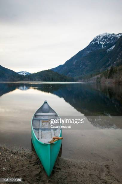 canoe moored on lakeshore at silver lake provincial park against mountains during sunset - moored stock pictures, royalty-free photos & images