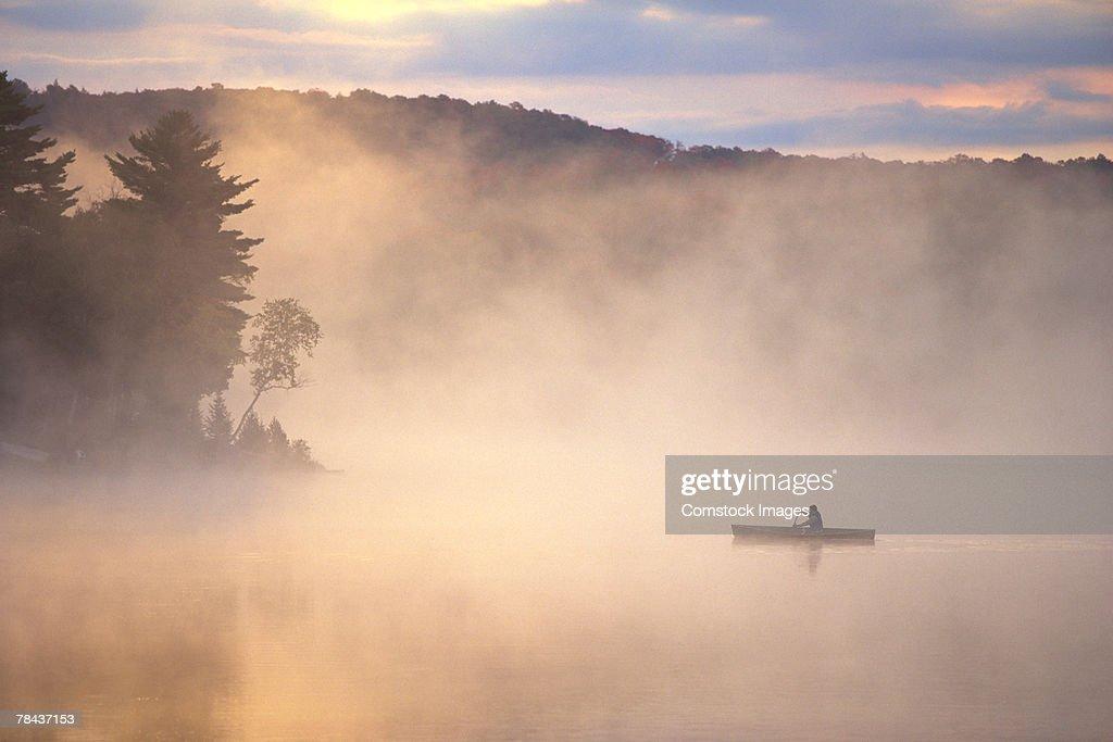 Canoe on a foggy lake : Stockfoto
