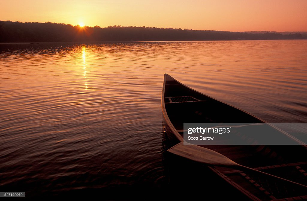 Canoe on a lake at sunset : Stock Photo