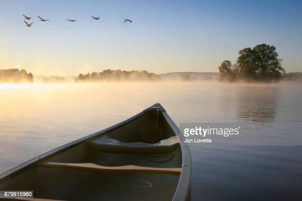 canoe on lake at sunrise - atmospheric mood stock pictures, royalty-free photos & images