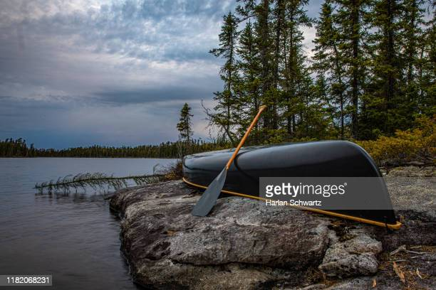 canoe on shore with storm approaching. - wilderness area stock pictures, royalty-free photos & images
