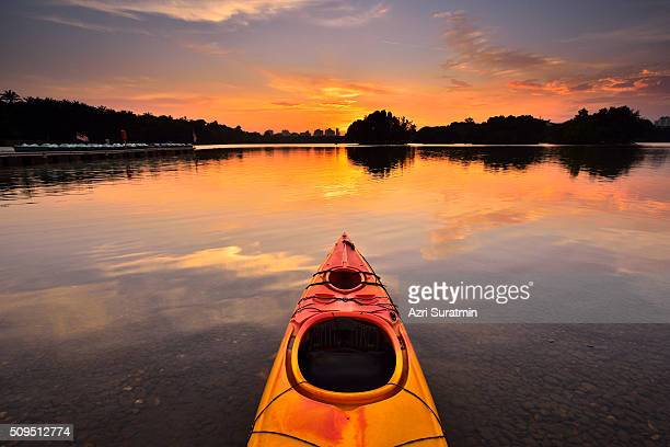 canoe on water during sunset - sunset lake stock photos and pictures