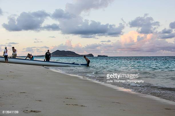 Canoe Paddlers Head in During a Pastel Colored Sunset in Teal Water at Lanikai Beach With the Mokapu Peninsula in the Distance Vacation Travel...