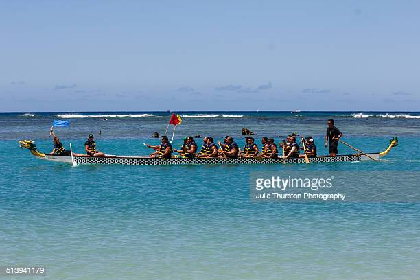 Canoe Paddling Teams Grab Flags While Competing in Colorful Carved Dragon Boat Racing in the Teal Blue Waters of The Pacific Ocean at Ala Moana Beach...