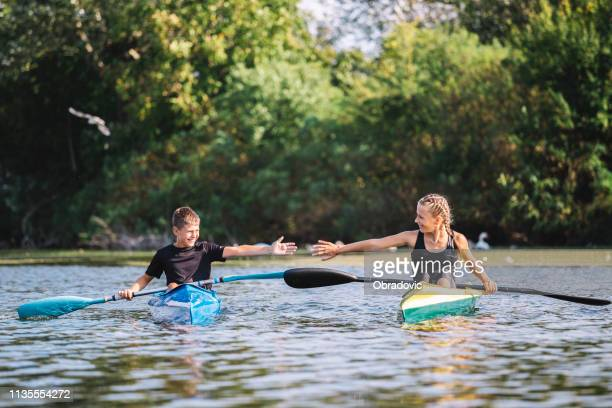 canoeing by the river. - paddling stock pictures, royalty-free photos & images