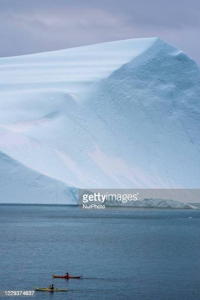Canoeist in front of Icebergs near Ilulissat, Greenland. Climate change is having a profound effect in Greenland with glaciers and the Greenland ice...