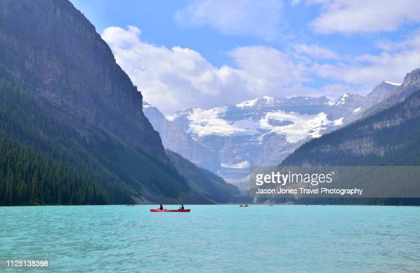 canoeists on lake louise - lake louise lake stock photos and pictures