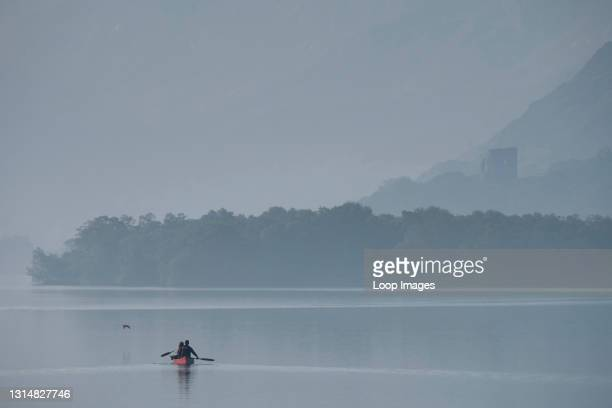 Canoeists on Llyn Padarn backed by Dolbadarn Castle and the Llanberis Pass in Snowdonia.