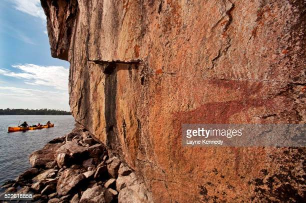 canoeists paddle by pictographs on lac la croix lake - boundary waters canoe area stock pictures, royalty-free photos & images