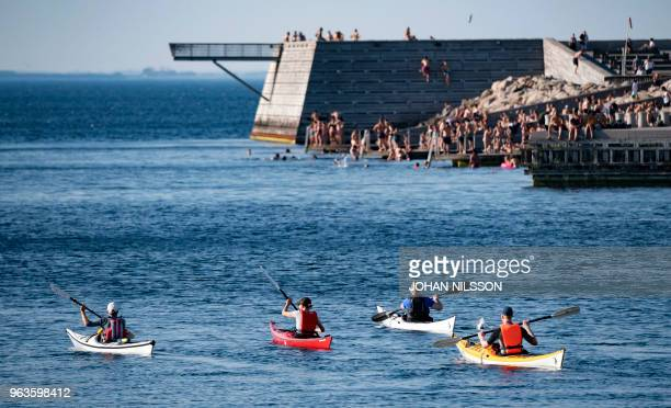 Canoeists paddle past a bathing jetty where people enjoy the cooling water in Malmo southern Sweden on May 29 2018 Sweden has enjoyed recordbraking...