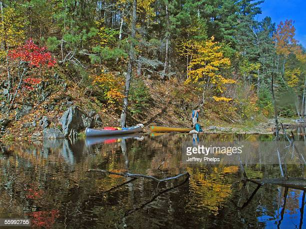 Canoeists rest along Mudro Lake in the Boundary Waters Canoe Area October 7, 2005 near Ely, Minnesota. The two man group was hunting for Moose in the...
