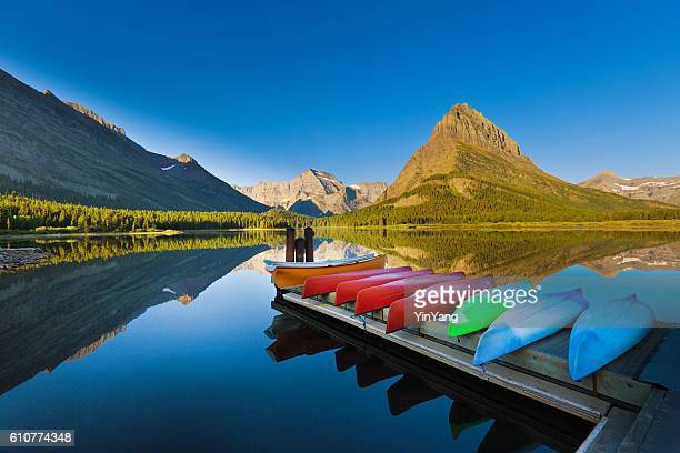 canoes at many glacier swiftcurrent lake glacier national park - north america stock pictures, royalty-free photos & images