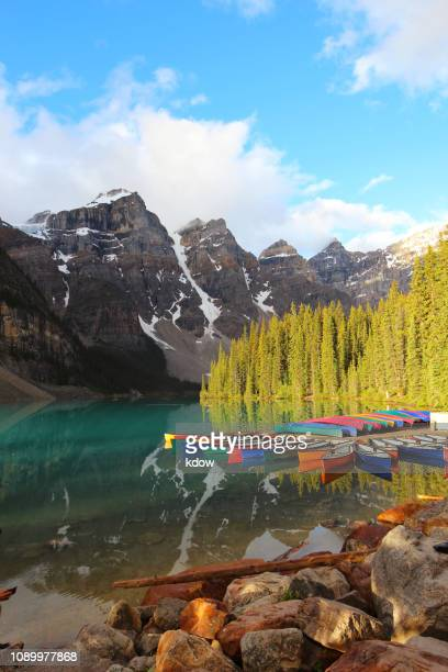 canoes by moraine lake in banff national park, alberta - lake louise stock photos and pictures