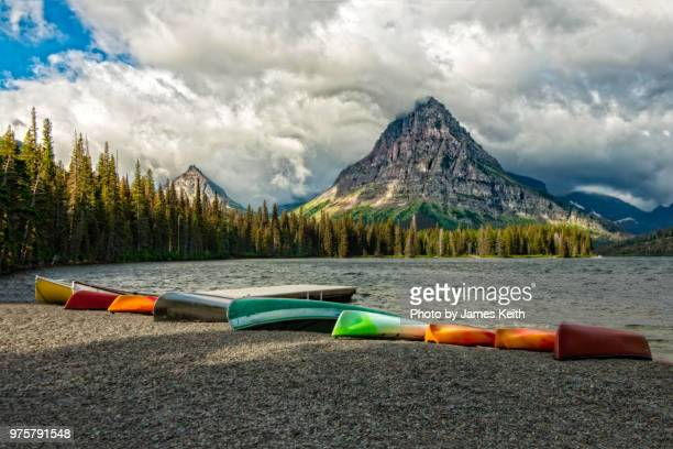 canoes lie on the shore awaiting a new day on two medicine lake in glacier national park. - two medicine lake montana fotografías e imágenes de stock