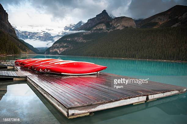 canoes on the dock - lake louise lake stock photos and pictures