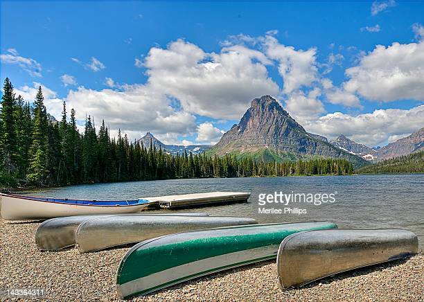 canoes waiting along shore of two medicine lak - two medicine lake montana stock-fotos und bilder