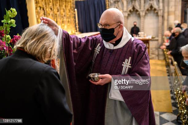Canon Barry Pyke sprinkles ash from burnt palm crosses from Palm Sunday in 2020 on members of the congregation as a token of penitence, during a...