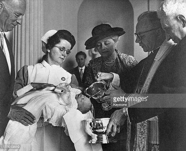 Canon Dewill performs the baptism ceremony of Prince Philippe of Belgium 23rd April 1960 The Prince is being held by a midwife as ExKing Leopold III...