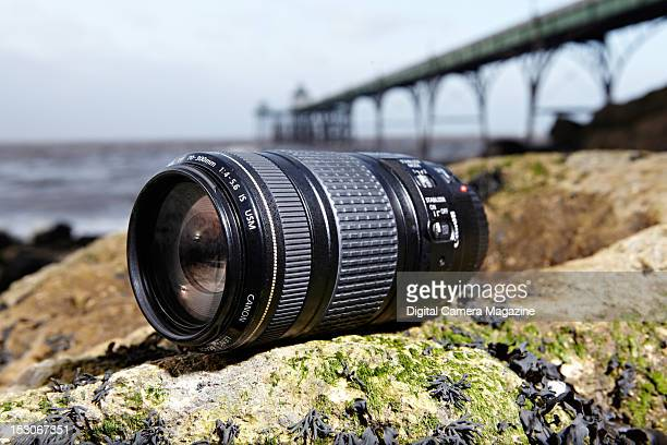 A Canon EF 70300mm f/456 IS USM camera lens on seaweedcovered rocks at Clevedon beach with Clevedon pier visible in the background taken on January 5...