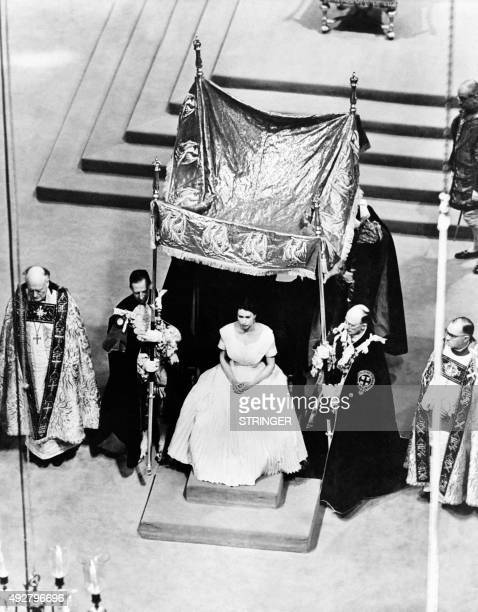 A canopy of cloth of gold is placed over Elizabeth II by the four Garter Knights prior to her anointing by the Archbishop of Canterbury at coronation...