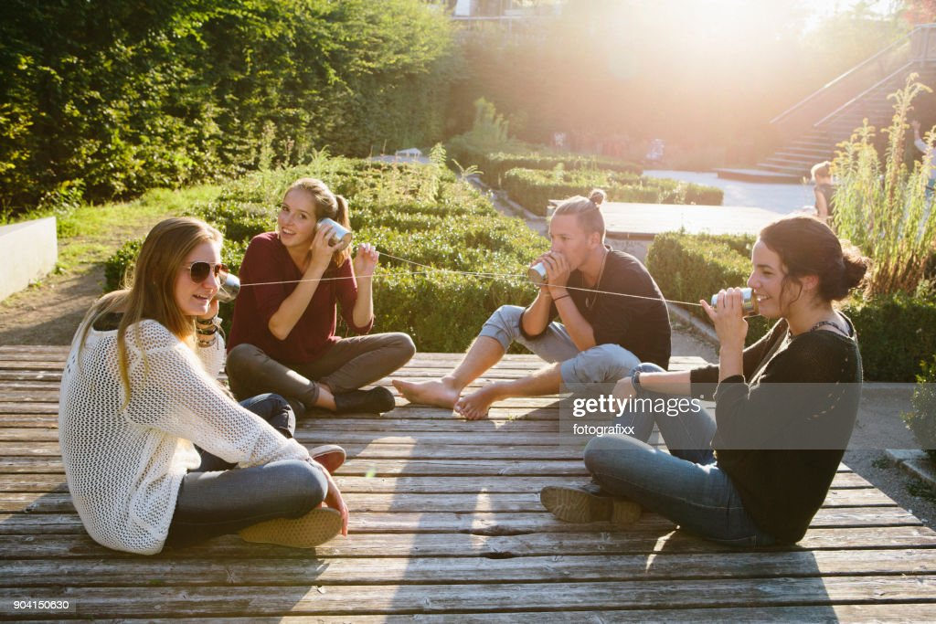 cans communication: young adults talking with tin can phones : Stock Photo