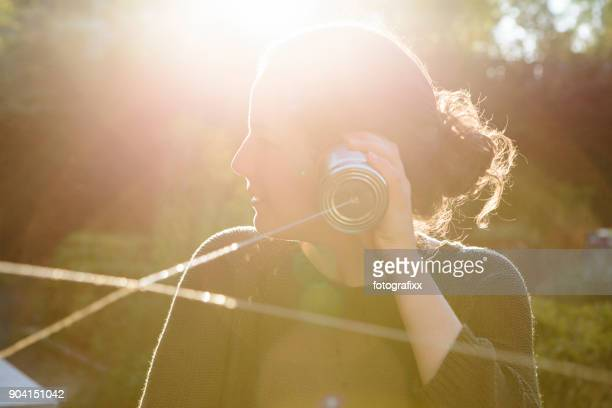 cans communication: young woman listens into tin can phone