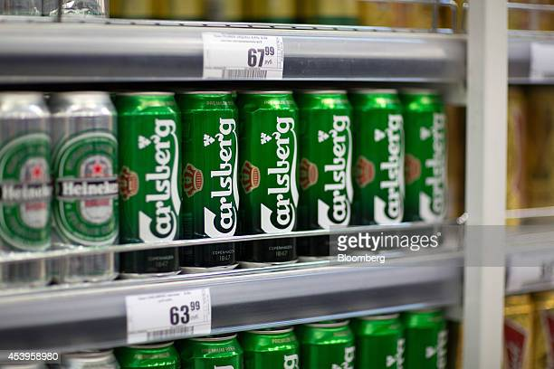 Cans of Carlsberg beer produced by Carlsberg A/S stand beside ruble price signs on shelves inside an X5 Retail Group NV's Perekrestok hypermarket in...