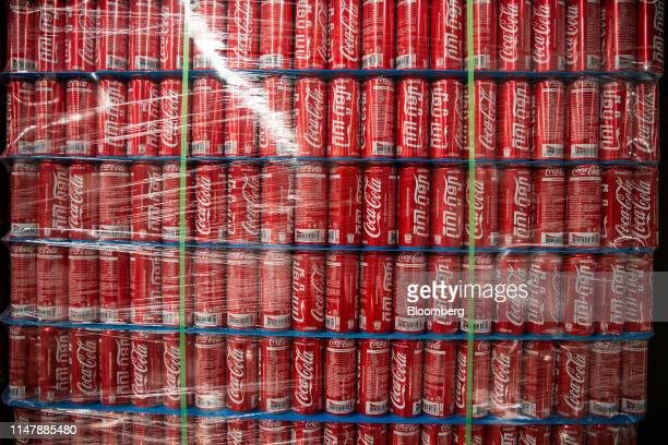 Cans of CocaCola Co brand Coke carbonated soft drink sit stacked inside a warehouse at the CocaCola Cambodia Bottling Plant operated by Cambodia...