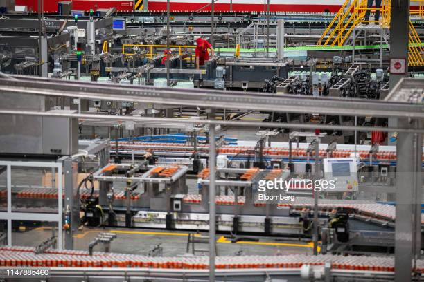 Cans of CocaCola Co brand Fanta carbonated soft drink foreground move along a conveyor at the CocaCola Cambodia Bottling Plant operated by Cambodia...