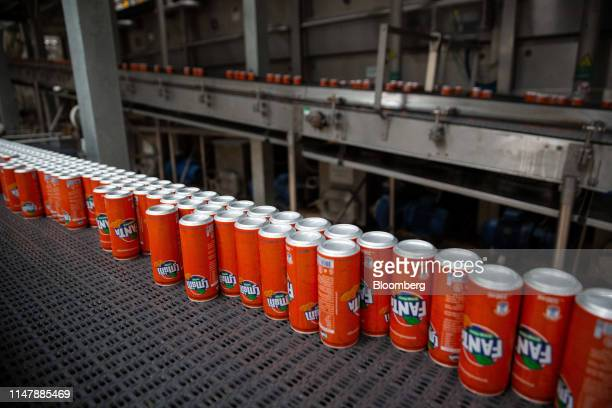 Cans of CocaCola Co brand Fanta carbonated soft drink move along a conveyor at the CocaCola Cambodia Bottling Plant operated by Cambodia Beverage Co...